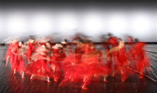 Group of ballet dancers wearing red in the middle of a routine on stage