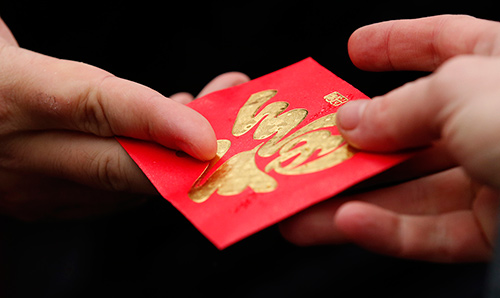 Close up image of two people handing over red envelopes