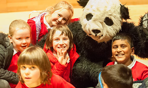 Children in primary school with someone in a panda costume