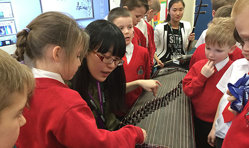 Children in a music workshop looking at a stringed instrument