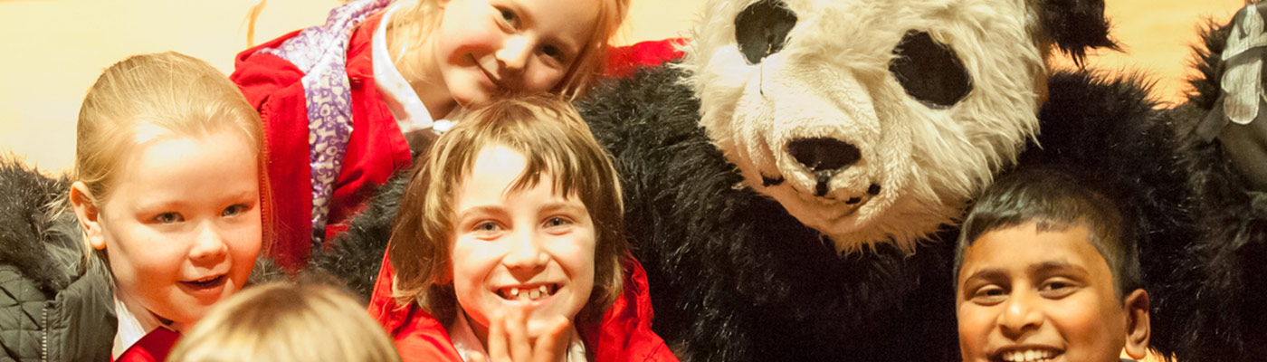 Children in primary school laughing with someone in a panda costume