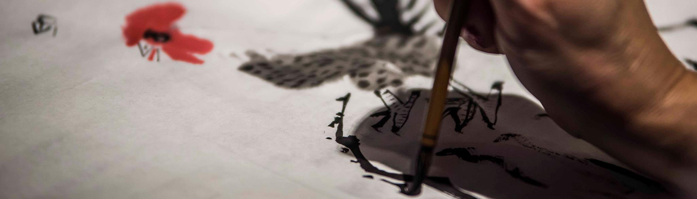Person writing with a paint brush on paper with black ink
